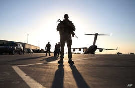 FILE - A solider stands guard near a military aircraft in Kandahar, Afghanistan.