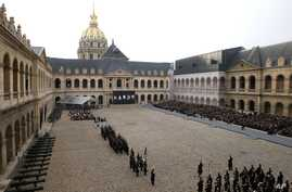 Guests, right, attend during a ceremony in the courtyard of the Invalides in Paris, Friday, Nov. 27, 2015.