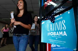 FILE - Two volunteers for President Barack Obama's re-election campaign, Carissa Valdez, right, and Vanessa Trujillo, left, leave campaign headquarters as they work to register new voters while they canvass a heavily Latino neighborhood shopping plaz...