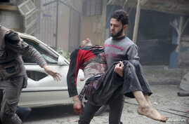 resident carries an injured man through a site damaged from what activists said was an airstrike by forces loyal to Syria's President Bashar al-Assad on the main field hospital in the town of Douma, Syria, Oct. 29, 2015.
