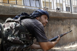 A Free Syrian Army fighter takes up his position during clashes in Aleppo, August 16, 2012.
