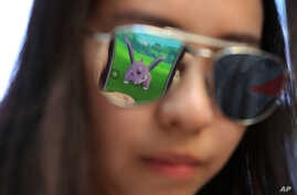"""A mobile screen is reflected on a fan's sunglasses as she plays """"Pokemon Go"""" in Hong Kong, July 25, 2016."""