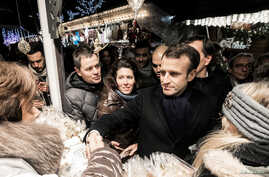 French President Emmanuel Macron shakes hands with visitors of the Christmas market in Strasbourg, France, Dec. 14, 2018.