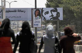 Palestinian girls walk near a billboard with a picture of US President Barack Obama, in the West Bank city of  Ramallah.