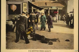 """This undated handout image provided by the Library of Congress shows a motion picture lobby card for D.W. Griffith's """"Broken Blossoms"""" (1919), showing sailors standing over two bodies, lying on the dirt street in Chinatown."""