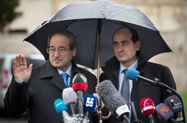 Syrian Deputy Foreign Minister Faisal Mekdad, left, as he arrives for a press briefing at the United Nations headquarters in Geneva, Switzerland, Feb. 10, 2014.