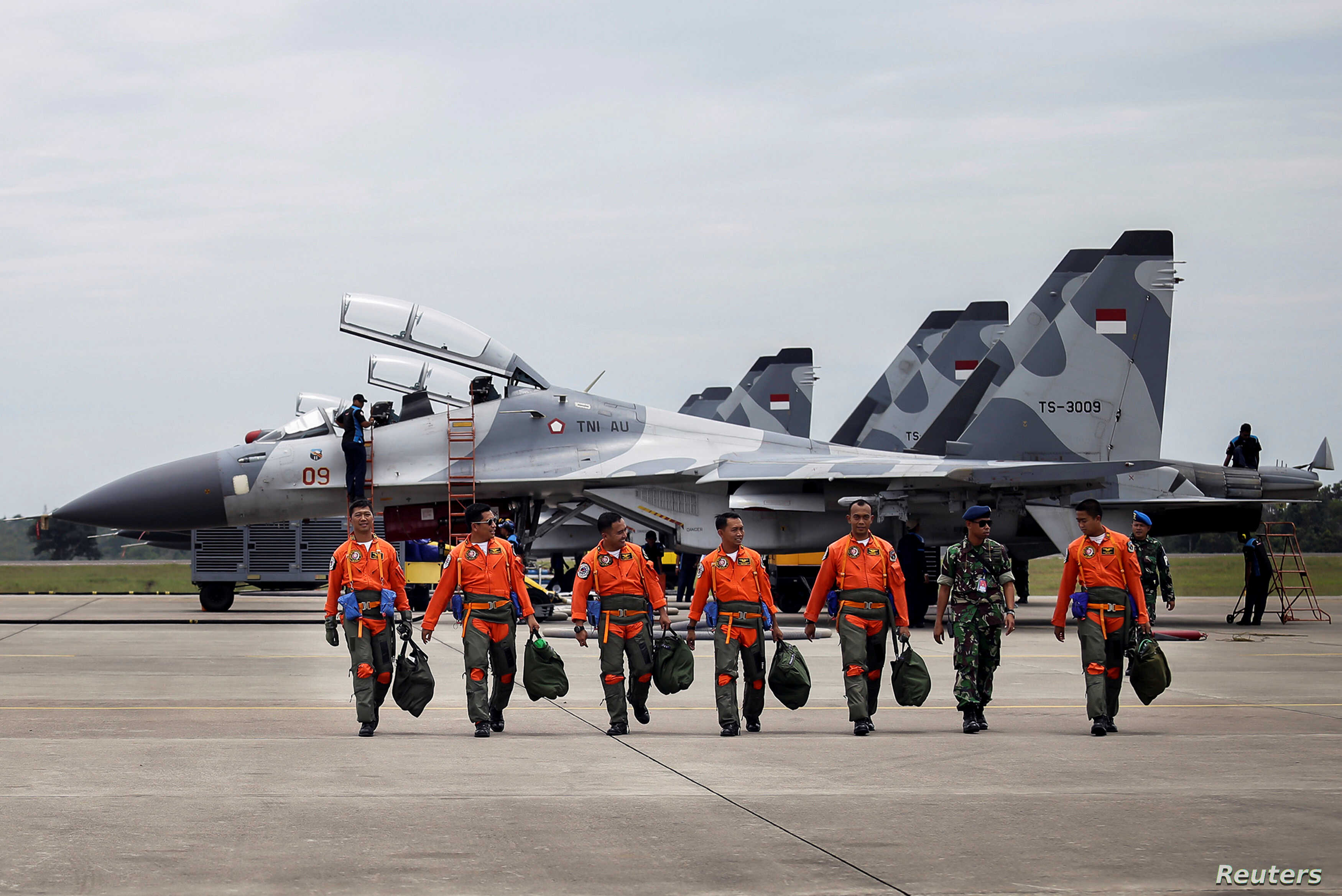 FILE -- Indonesian Air Force Sukhoi fighter pilots and crew walk across the tarmac at the Hang Nadim Airport after training for an upcoming military exercise, October 3, 2016.