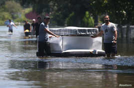 People use an air mattress to float possessions out of a flooded area of Port Arthur, Texas, Aug. 31, 2017.