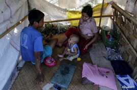 Members of a homeless family pass the time in their temporary shelter beside a street in Yangon, Myanmar,  Feb. 4, 2016.