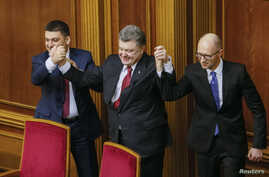 Ukraine's President Petro Poroshenko, center, holds up the hands of newly appointed Prime Minister Arseny Yatseniuk, right, and newly appointed Parliament Speaker Volodymyr Groysman during a parliament session in Kyiv, Nov. 27, 2014.