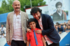 """Turkish director Kaan Mujdeci (R), actor Dogan Izci (C) and actor Muttalip Mujdeci arrive for the screening of the movie """"Sivas"""" presented in competition at the 71st Venice Film Festival on Sept. 3, 2014 at Venice Lido."""