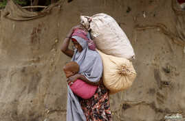 A displaced Somali woman carries a child and her belongings as she arrives at a temporary dwelling after fleeing famine in the Marka Lower Shebbele regions to the capital Mogadishu, Sept. 20, 2014.