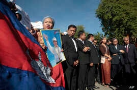 A supporter of the opposition Cambodia National Rescue Party holds a poster of the party leader Kem Sokha during a rally joined by lawmakers near an appeals court in Phnom Penh, Cambodia, Sept. 26, 2017.