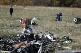 Members of a recovery team work at the site where downed Malaysia Airlines flight MH17 crashed, near the village of Hrabove, Donetsk region, eastern Ukraine, Oct. 13, 2014.