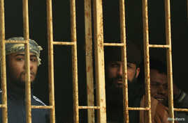 Prisoners are seen behind bars in a Benghazi jail in this February 22, 2012, file photo.