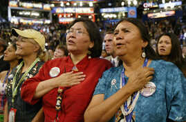 FILE: Native American delegates from Washington state listen to the national anthem, sung in the traditional Tohono O'odham language, during the Democratic National Convention in Boston, Tuesday, July 27, 2004.