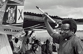 Bishop Abel Muzorewa, member of executive council and leader of UANC, shows voters how to vote by signing a cross near crest of his party during Rhodesian general elections, 19 Apr 1979
