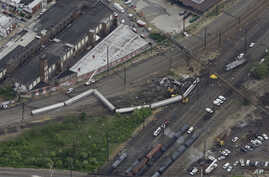 FILE - Emergency personnel work at the scene of a deadly train derailment in Philadelphia, May 13, 2015.