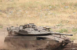 An Israeli tank drives in the Israeli-controlled Golan Heights, near the border with Syria, May 10, 2018.