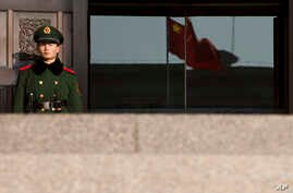 FILE - A paramilitary policeman stands guard at an entrance of China's Supreme Court in Beijing.