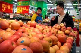 A woman wearing a uniform with the logo of an American produce company helps a customer shop for apples a supermarket in Beijing, China, March 23, 2018.