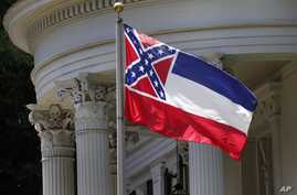 FILE - The Mississippi state flag is unfurled against the front of the Governor's Mansion in Jackson, Mississippi, June 23, 2015.