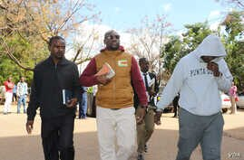 Holding a Bible, Pastor Evan Mawarire walks into the court building while handcuffed to his driver, Ocean Chihota, in Harare, Zimbabwe, June 28, 2017. (S. Mhofu/VOA)
