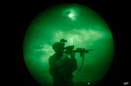 A U.S soldier patrols at night in Khost province, Afghanistan, seen through night vision equipment. About 400,000 veterans had a PTSD diagnosis in 2013, according to the Veterans Affairs health system.