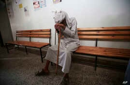 FILE - An elderly man waits to be treated for a suspected cholera infection at a hospital in Sana'a, Yemen, July 12, 2017.