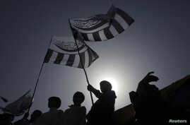 Supporters of the Jamaat-ud-Dawa Islamic organization are silhouetted against the sun as they raise their party flags while taking part in an anti-American rally in Lahore May 25, 2012. About 150 protesters gathered to take part in a protest rally ag