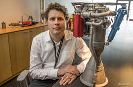 FILE - Rocket Lab CEO Peter Beck sits alongside a Rutherford rocket engine in Auckland, Oct. 20, 2015.