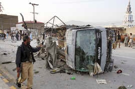 A Pakistani police officer walks past a police vehicle targeted by a suicide bomber in Quetta, April 24, 2018.