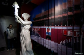 A visitor looks at a statue of the Goddess of Democracy at Hong Kong's museum dedicated to the Tiananmen Square pro-democracy protests, in Tsim Sha Tsui, Apr. 26, 2014.
