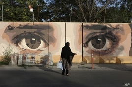An Afghan woman waits for transportation in front of street art on a barrier wall of the NDS (National Directorate of Security) in Kabul, Afghanistan, Aug. 20, 2015.