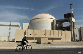 FILE - A worker rides a bicycle in front of the reactor building of the Bushehr nuclear power plant, just outside the southern city of Bushehr, Iran.