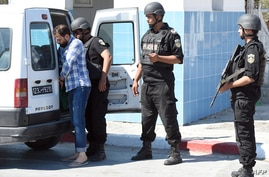 Tunisian security forces man a checkpoint at the entrance of the resort area on the outskirts of Sousse south of the capital Tunis following a shooting attack at the beach resort Friday, June 27, 2015.
