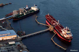 FILE - Oil tankers Qi Lin Zuo of China and Sti-Matador, left, stand attached to mooring stations near a refinery in Bayonne, New Jersey, Aug. 24, 2011. Crude oil is among the U.S. products China has said it will impose tariffs on but has yet to anno