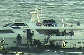 In this video image released by the Israeli Defense Ministry on November 4, 2011, Israeli soldiers on several small military boats appear to board a civilian boat believed to be one of two protest boats trying to violate Israel's blockade of the Gaza