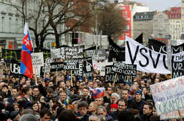 Demonstrators call for elections at a protest rally, in Bratislava, Slovakia, March 16, 2018, saying the prime minister's resignation is not enough following the murder of Slovak investigative reporter Jan Kuciak and his fiancee, Martina Kusnirova.