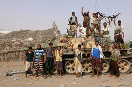 FILE - Tribal fighters loyal to the Yemeni government stand by a tank in al-Faza area near Hodeida, Yemen, June 1, 2018.