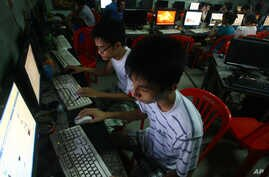 FILE - two Vietnamese students use Facebook at an internet cafe near their dormitory while they could not log in Facebook from their mobile phones because of firewall in Hanoi, Vietnam.
