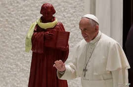 Sweden Pope's Visit: In this photo taken on Oct. 13, 2016, Pope Francis passes by a statue portraying Martin Luther as  he arrives for an audience with Lutheran pilgrims at the Vatican. Pope Francis travels to Sweden next week to commemorate the spli