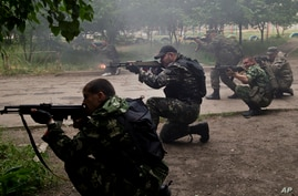 Pro-Russian rebels fire weapons during clashes with Ukrainian troops on the outskirts of Luhansk, Ukraine, June 2, 2014.