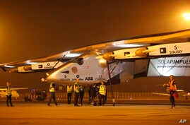 Crew members gather to push the Solar Impulse 2 towards a hangar after it landed at an airport in Ahmadabad, India, March 11, 2015.