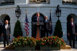 President Donald Trump delivers remarks about the economy on the South Lawn of the White House, July 27, 2018, in Washington. From left, Commerce Secretary Wilbur Ross, Trump, Vice President Mike Pence, and Treasury Secretary Steve Mnuchin.