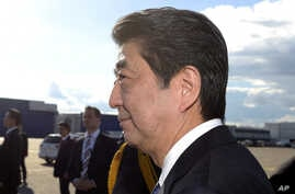 Japanese Prime Minister Shinzo Abe, foreground and his wife Akie arrive at the Helsinki International Airport in Vantaa, Finland, Sunday, July 9, 2017.