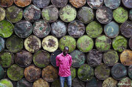 Steel barrel vendor Lassiney Diarra poses for a picture in front of barrels in Bamako, Mali, Aug. 13, 2013.