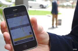 Anton van Metzinger shows how the SnappCab application works on his smartphone. He and his two business partners launched their app in September, which allows users to hail a cab and pay for it within the application, Johannesburg. (Peter Cox for VOA