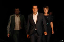 Greek Prime Minister Alexis Tsipras, center, leaves the Presidential palace after a meeting with Greek President Prokopis Pavlopoulos, in Athens, on Thursday, Aug. 20, 2015.