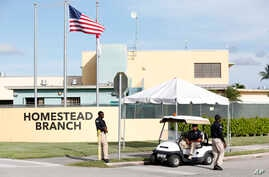 Security guards stand outside a former Job Corps site that now houses child immigrants,  June 18, 2018, in Homestead, Fla. It is not known if the children crossed the border as unaccompanied minors or were separated from family members.